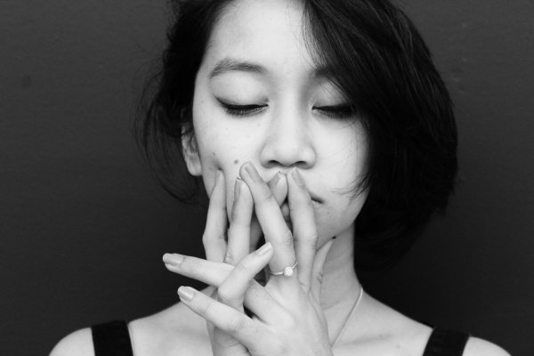 Black and white photo of a woman with her eyes close holding her hands to face,