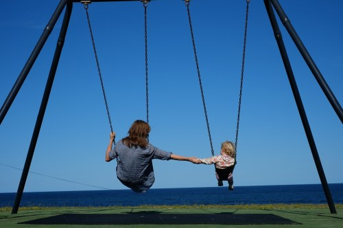 mom and daughter sitting on a park swing