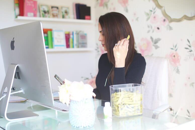 brunette woman in feminine office snacking on snap pea crisps | how to stay energized throughout the day as a busy mom