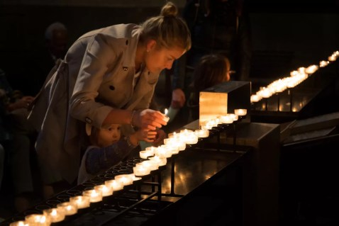 Mother and child lighting votive candles in the Dom.