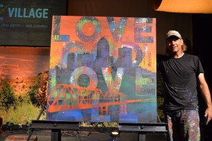 "William Butler, artist from Camden, NJ, poses with his ""Love God. Love All."" painting he crafted at The Downtown Church in Des Moines, Iowa."