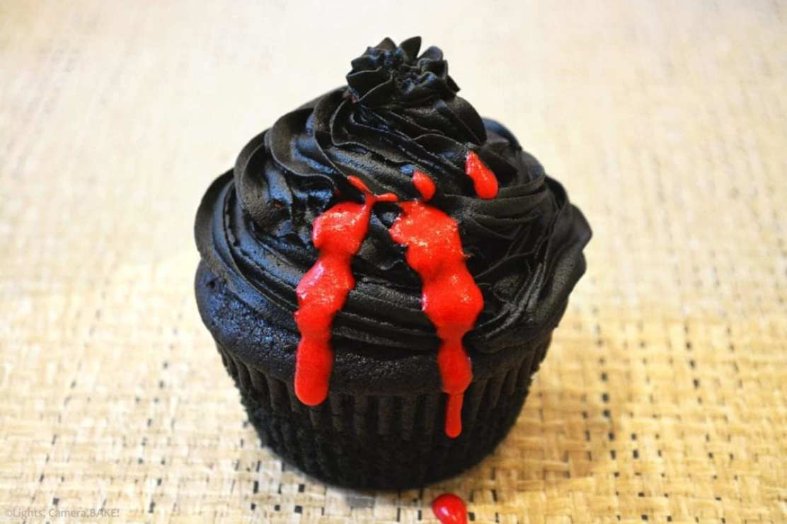 Vampire Cupcakes are a black velvet cupcake with a black, chocolate buttercream, filled with a white chocolate ganache dyed red for the blood filling.
