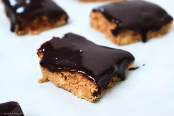 No Bake Chocolate Peanut Butter Bars are a crushed digestive biscuit (graham cracker) and peanut butter base with a rich chocolate ganache topped bar. These are crunchy sweet and taste just like a Reeces Peanut Butter Cup.