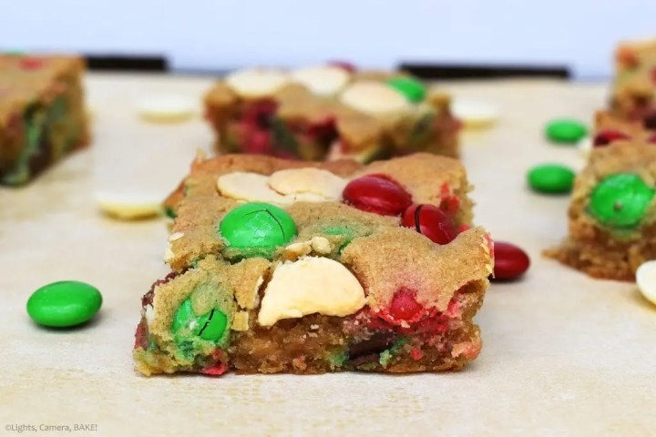Christmas Cookie Bars are soft and gooey spiced cookie bars with white chocolate buttons and Christmas themed M&Ms. #christmasrecipe #mandmcookies #cookiebars #mandmcookiebars #christmascookiebars