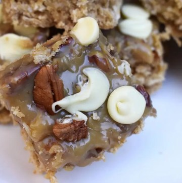 Caramel Pecan Oat Slice is a chewy oat slice studded with chocolate chips and topped with caramel, coconut, pecans and white chocolate. #caramelslice #carameloatbars #pecanoatbars #caramelpecanoatbars #pecancaramel #oatslice #oatmealbars