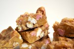 White background with slices of Caramilk rocky road in a pile.