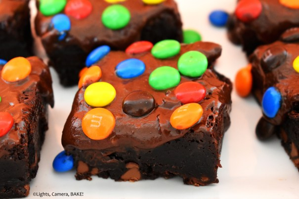 Close up of M&M covered cosmic brownies on a white plate.