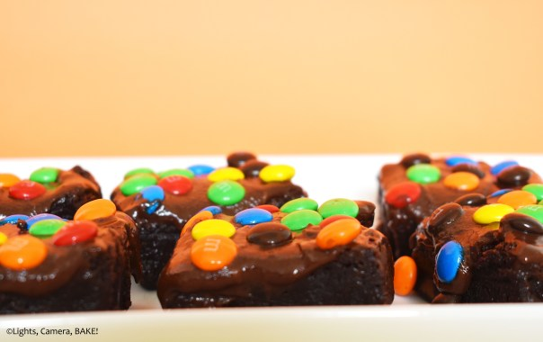 M&M covered cosmic brownies on a white plate with an orange background.