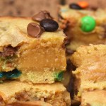 Close up of a caramel filled M&M cookie bars with a brick background.