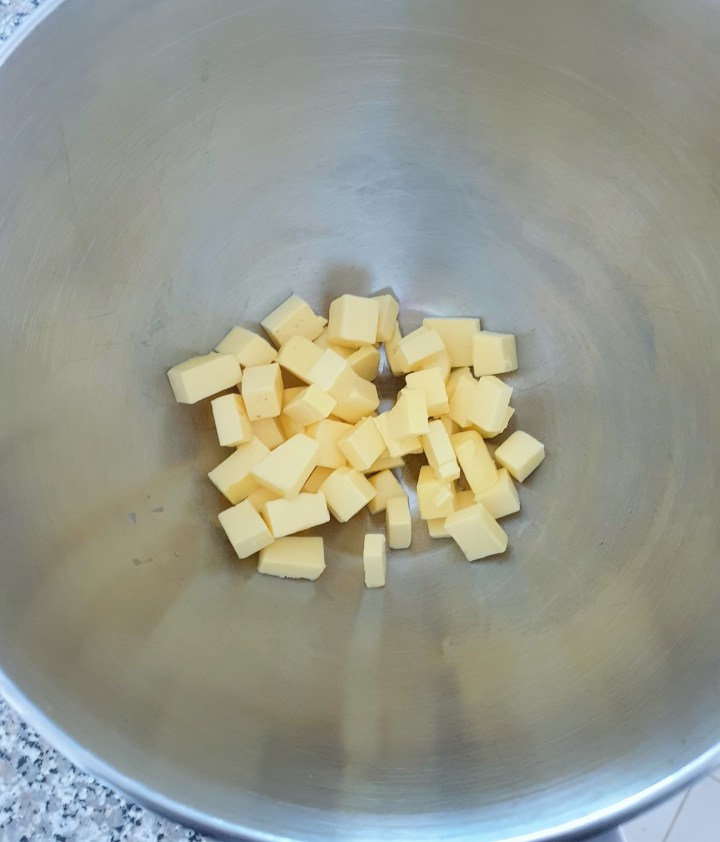 Cold butter in a stainless steel bowl.