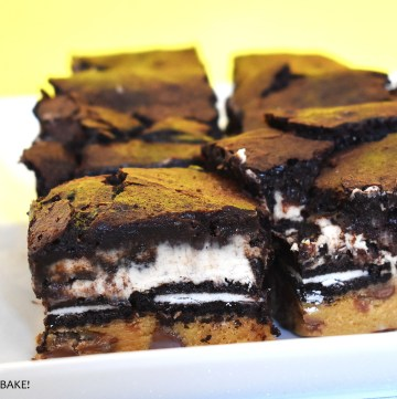 Oreo cheesecake brownies on a yellow background.