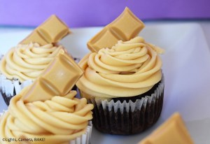 Chocolate cupcakes with caramilk buttercream on a purple background.