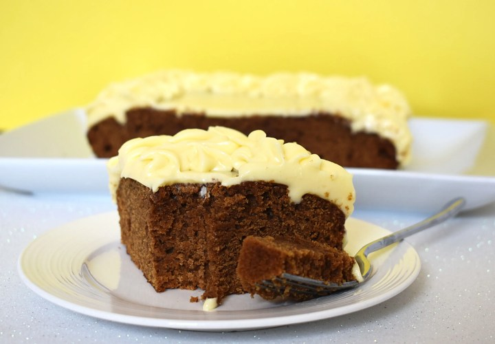 Slice of gingerbread cake with cream cheese icing.