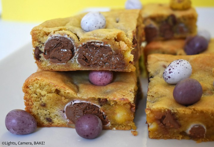 Stack of mini egg cookie bars on a yellow background.