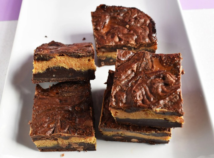 Slices of caramel filled brownies on a white plate.