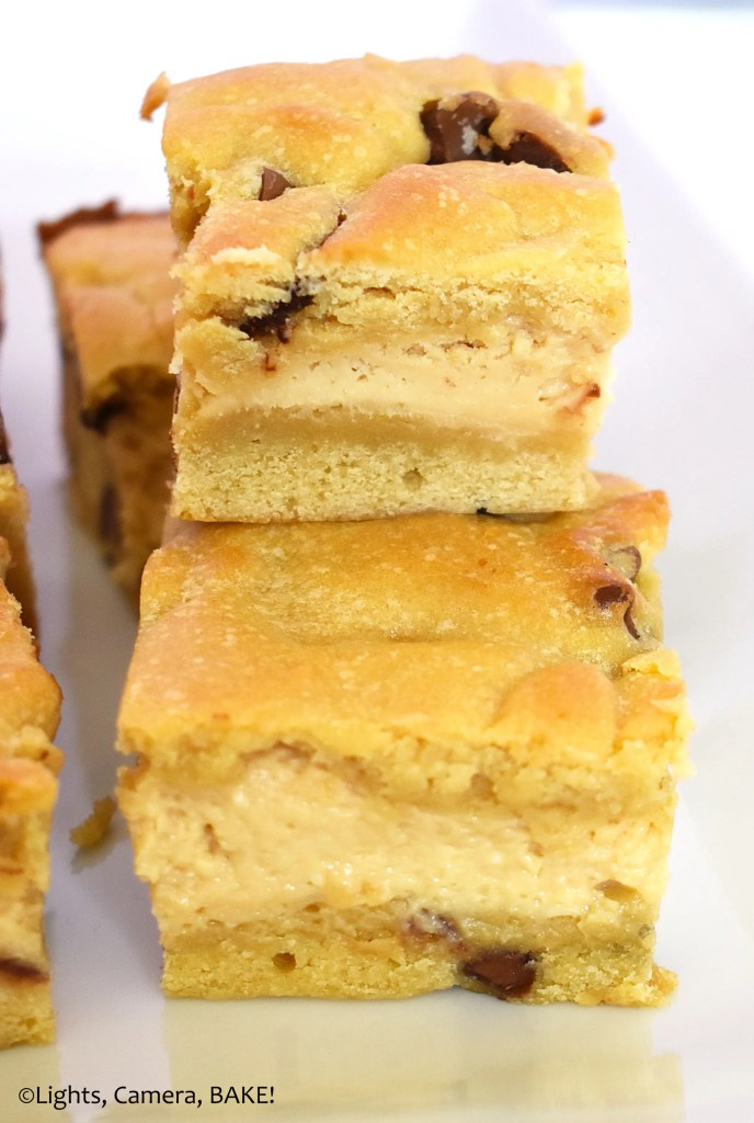 Pieces of caramilk cheesecake cookie bars on a plate.