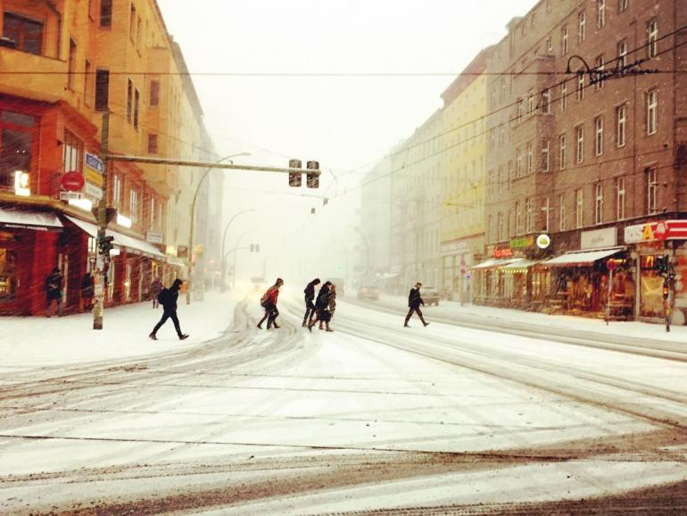 Descrição para deficientes visuais: a imagem mostra pessoas atravessando a rua coberta de neve. Em contraste com o frio intenso, os prédios nas laterais são pintados com cores quentes, como vermelho, laranja e amarelo. — at Eberswalder Straße.