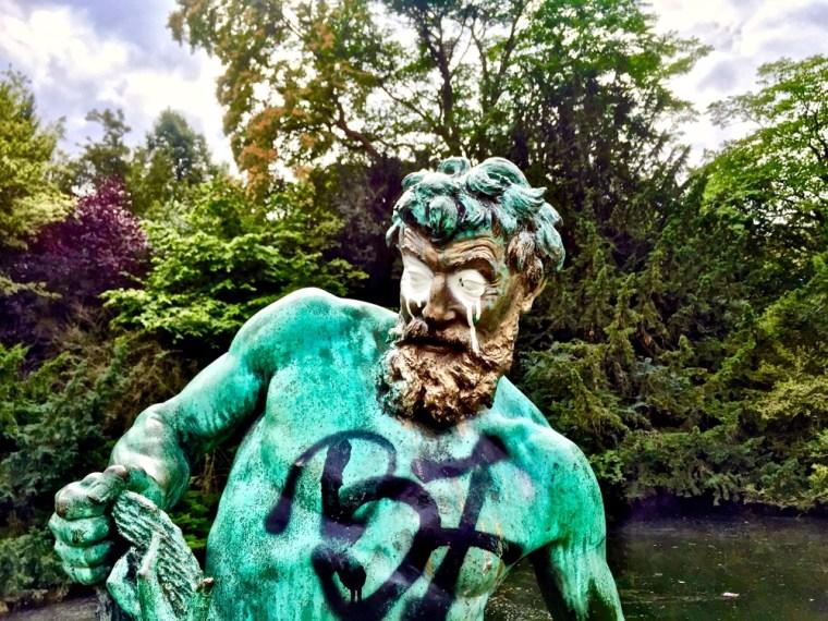 A imagem mostra a escultura de um homem, toda vandalizada e pixada, como um Atlas que já está cansado de ser explorado e não reconhecido.