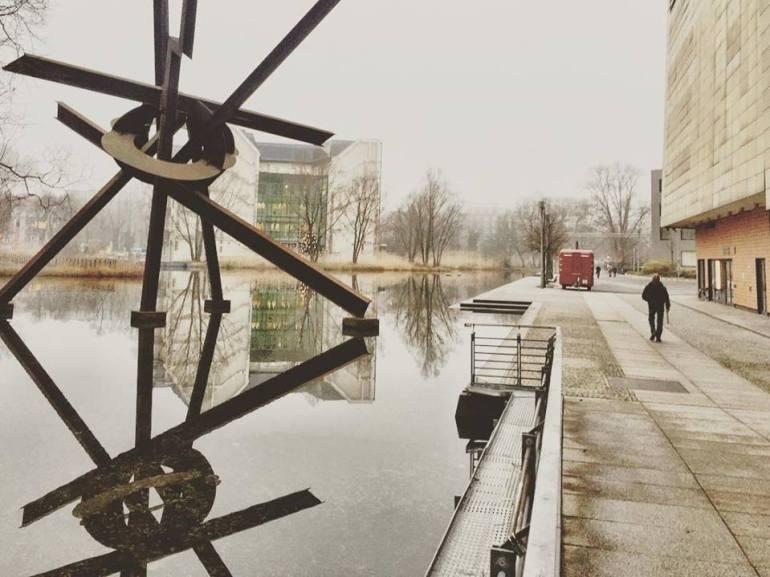 #paracegover Descrição para deficientes visuais: a imagem mostra um homem caminhando em uma calçada, do lado direito. Do lado esquerdo, um lago que reflete a escultura formada por tubos. A névoa toma conta de tudo, forjando um clima de mistério e suspense... — at Theater am Potsdamer Platz.