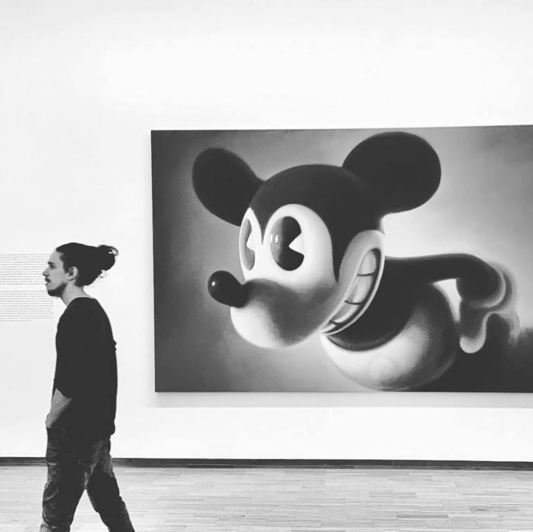 """#paracegover Descrição para deficientes visuais: a imagem mostra a obra """"Pink Mouse 2"""" do artista austríaco Gottfried Helnwein, onde um Mickey Mouse um tanto quanto sinistro (uma crítica aos desenhos animados pós Segunda Guerra) olha para o lado, justamente na hora em que está passando um rapaz de dreads amarrados em coque, visitante do museu. O quadro é em tons de pink, mas achei que a versão em preto e branco ficou com um contraste melhor. — at Albertina Museum."""