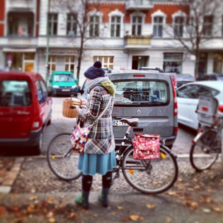 #paracegover Descrição para deficientes visuais: a imagem mostra uma moça muito elegante cheia de cachecóis, touca, casacos e luvas preparando-se para sair com sua bicicleta. Mesmo com frio e tempo chuvoso, o povo aqui é muito valente! — in Prenzlauer Berg, Berlin, Germany.