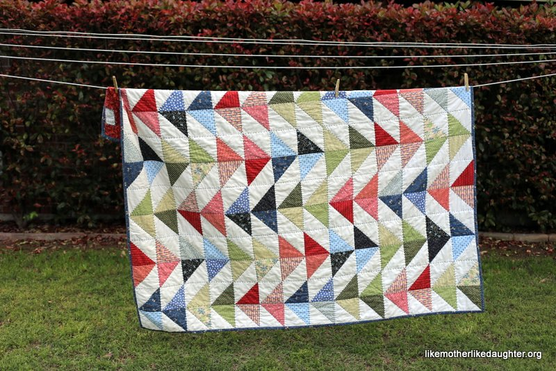 A bright and colorful modern half-square triangle quilt for a little boy's big boy bed.