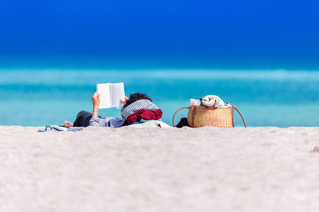 Beach Reads: Person reading a book on the beach