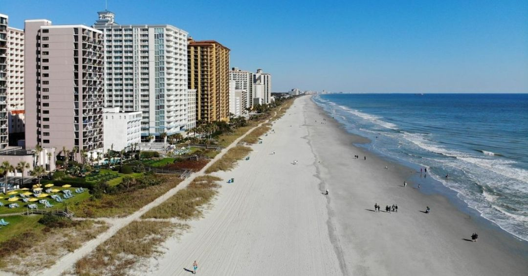 A strip of beach in Myrtle Beach with highrise hotels lining it