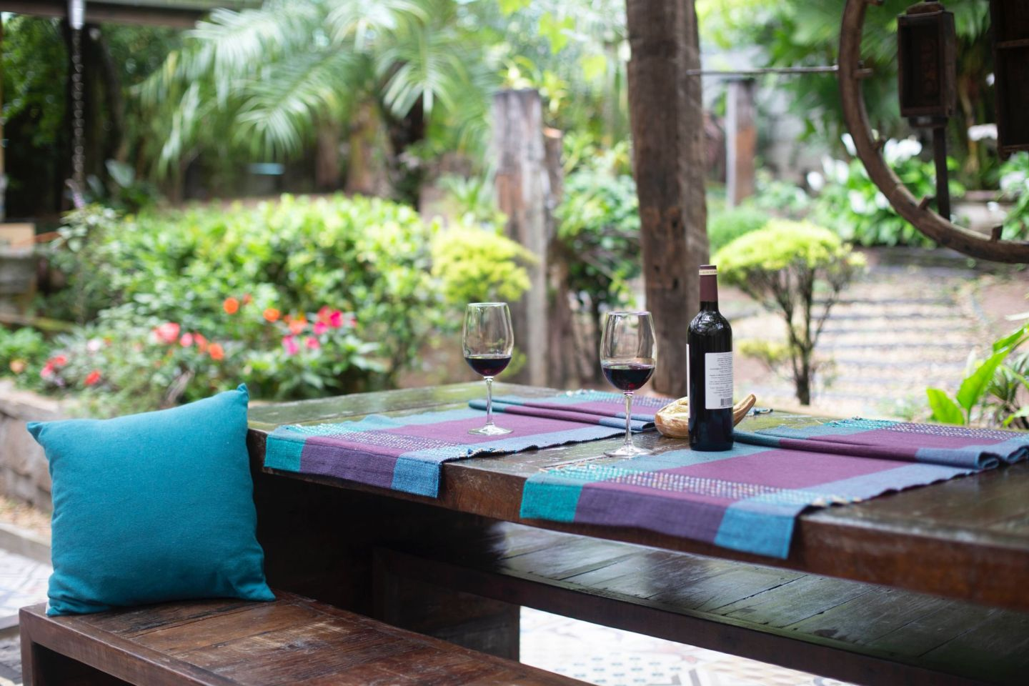 Cosy garden table and bench with laid with mats, matching cushions and wine . Get your garden ready to entertain