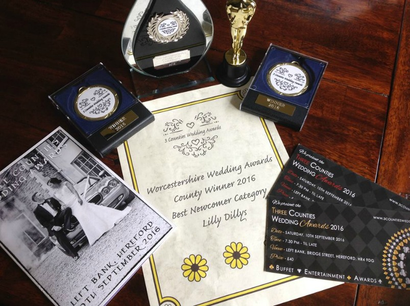 Image of all the Three Counties wedding awards on a wooden table next to Three Counties Wedding Awards flyer and tickets