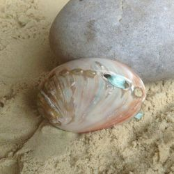 Image of Lilly Dilly's shell ring holder next to a pebble on the sand
