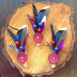 Image of Lilly Dilly's bespoke button holes made using feathers and a button laid on a slice of wood