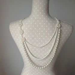 Image of Lilly Dilly's bespoke pearl back drape jewellery draped on a polkadot dressmakers mannequin