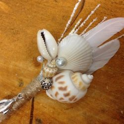 Close up image of Lilly Dilly's bespoke button holes made with sea shells and white feathers laid on a slice of wood