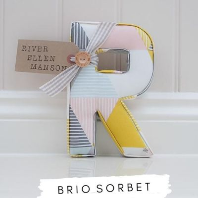 Fabric Letters Brio Sorbet fabric. White fabric with pink, blue and yellow triangles. Personalised nursery letter R with name tag River Ellen Manson. Gift for baby girl