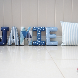 Cushion cover made using Clarke & Clarke Party Stripe Sky fabric along with fabric letter nursery initial letters Jamie J Navy with white stars, A Dark blue striped, M Blue and grey geometric pattern, I Navy white cloud pattern, E Dotty baby blue fabrics. Studio G Clarke & Clarke Lilymae Designs