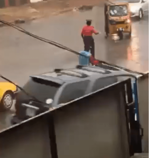 Traffic warden praised by social media users for controlling traffic under the rain in Ilorin