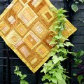 Modern yellow quilt on gray wall