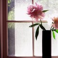 vase of pink peonies on a window sill brings the outdoors indoors