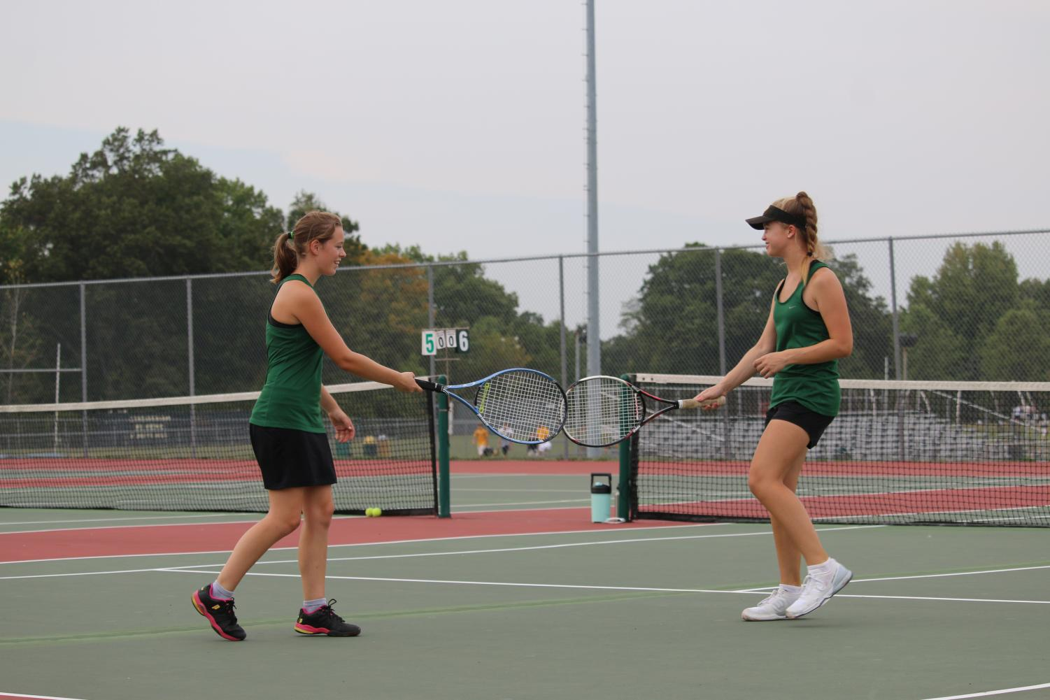 Melanie Ford (12) and her partner exchange a racquet tap after a match well played.