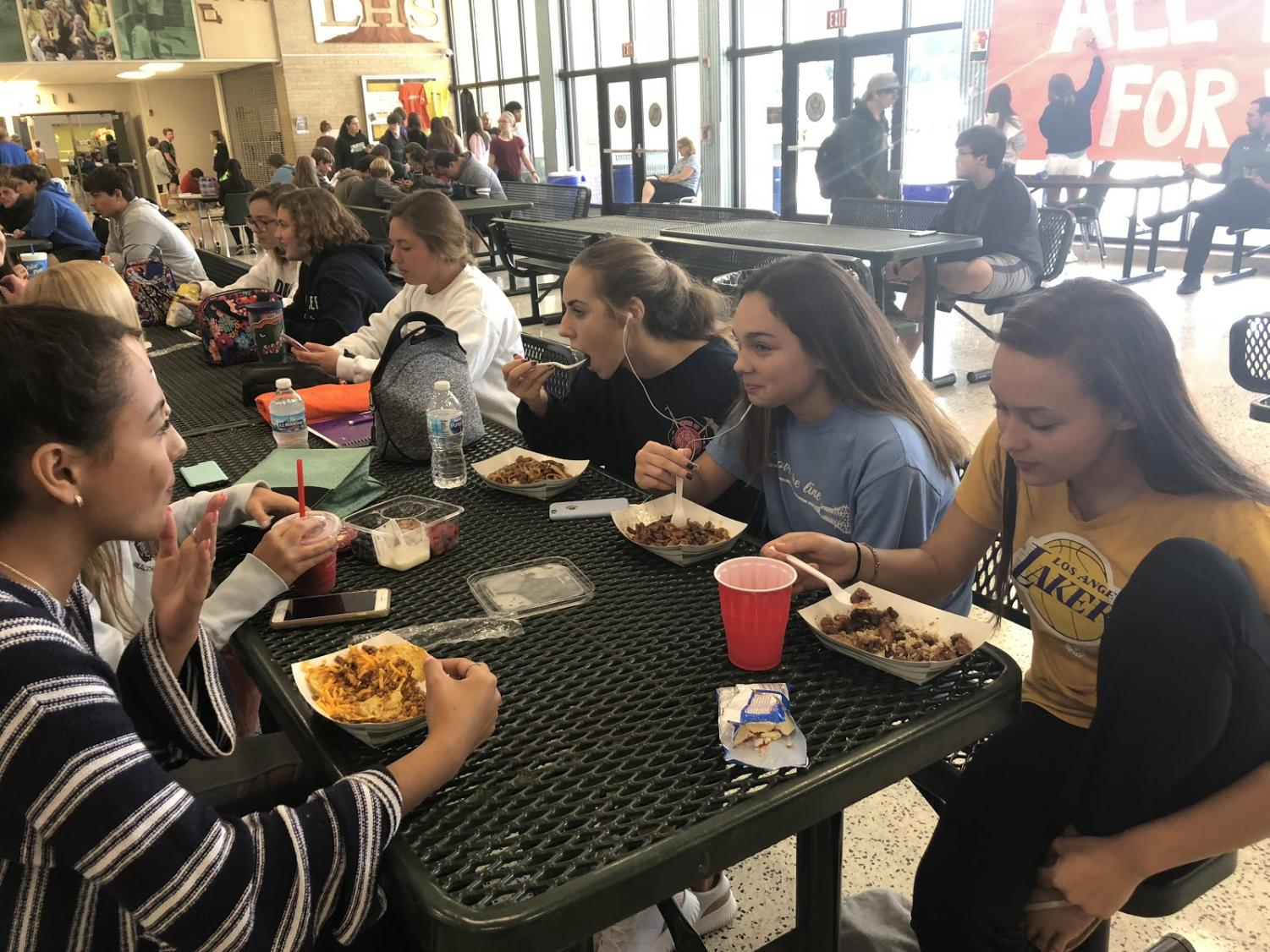A group of sophomore girls visit while eating their school lunches. The school vamped up their options at the start of the school year.