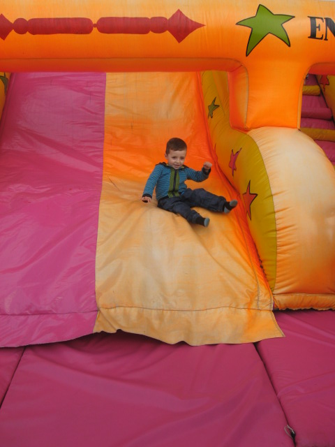Young child sliding down an inflatable slide