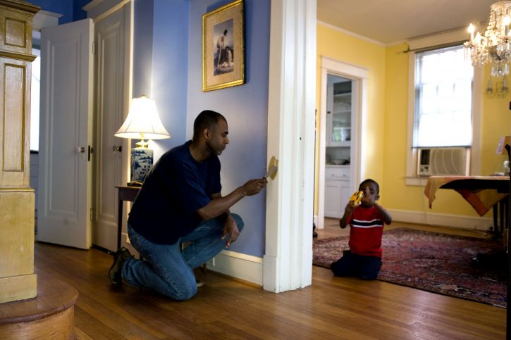 man-painting-an-interior-door-frame-at-home-with-his-young-son-725x483