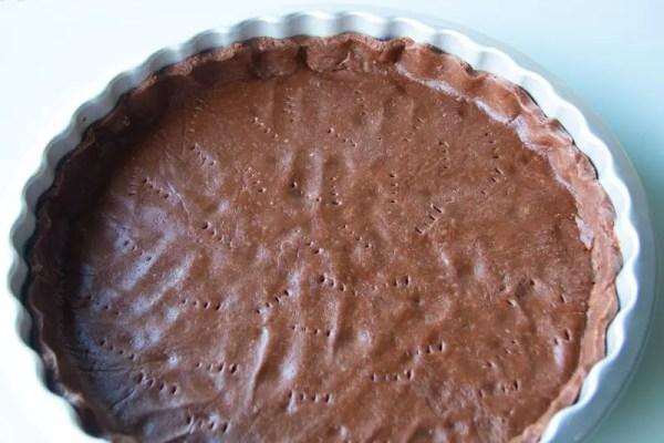 Une pâte sablée au cacao et à la poudre d'amandes dans son moule
