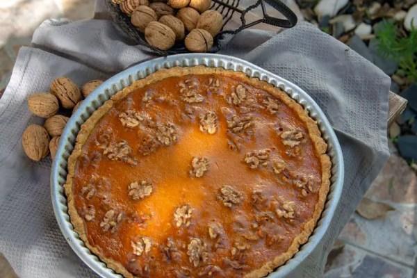 Tarte rustique au potimarron et aux noix dans son moule entourée de noix