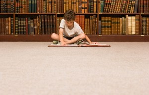 Boy reading book in library