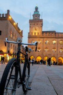 Foto di piazza Maggiore, Bologna, Italia. In primo piano una bicicletta e sullo sfondo piazza Maggiore illuminata