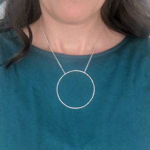 hammered sterling silver focal necklace on a teal shirt