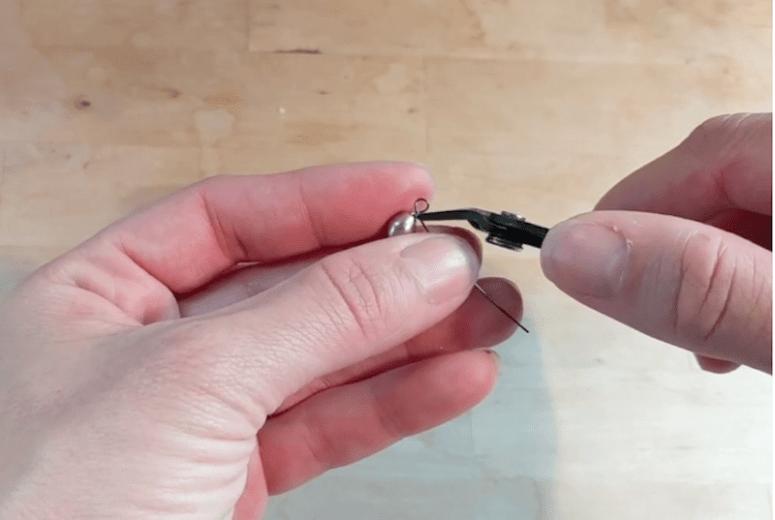 hand making eye pin loop with a purple bead