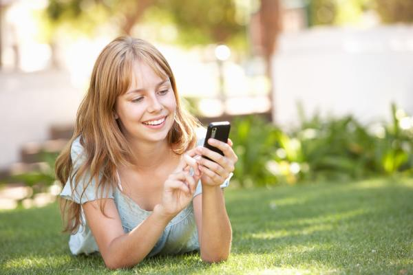 Teenage Girl Laying In Park Using Mobile Phone Linn Area
